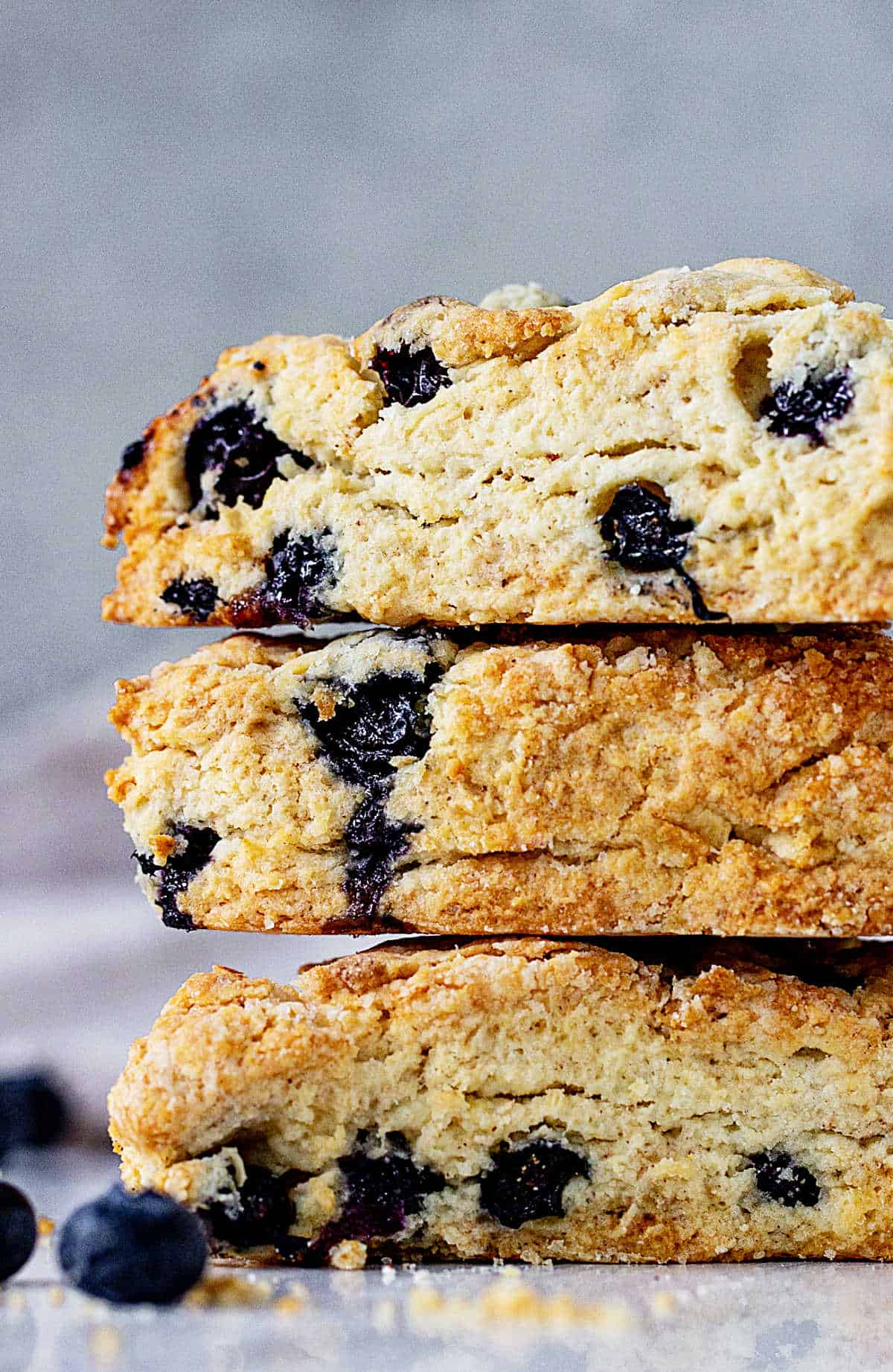 Very close up of partial stack of blueberry scones, grey blue background
