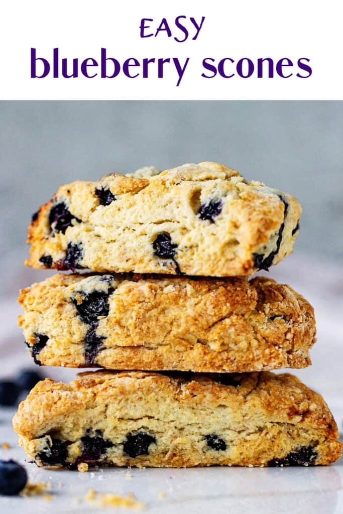 Stack of scones with blueberries on white surface and grey background; purple text on top