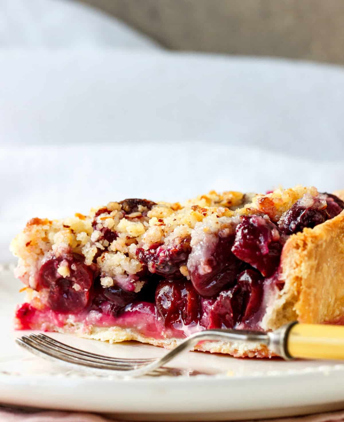 Close up of cherry pie slice on white plate and background