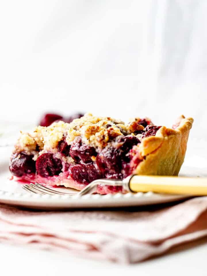 White background and plate with cherry pie slice, a fork, light pink napkin underneath