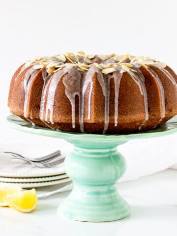 A whole bundt cake on a green cake stand, white background, lemon wedges, plate stack