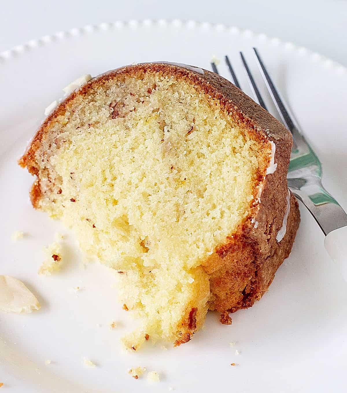 Close up of bitten slice of lemon bundt cake on white plate