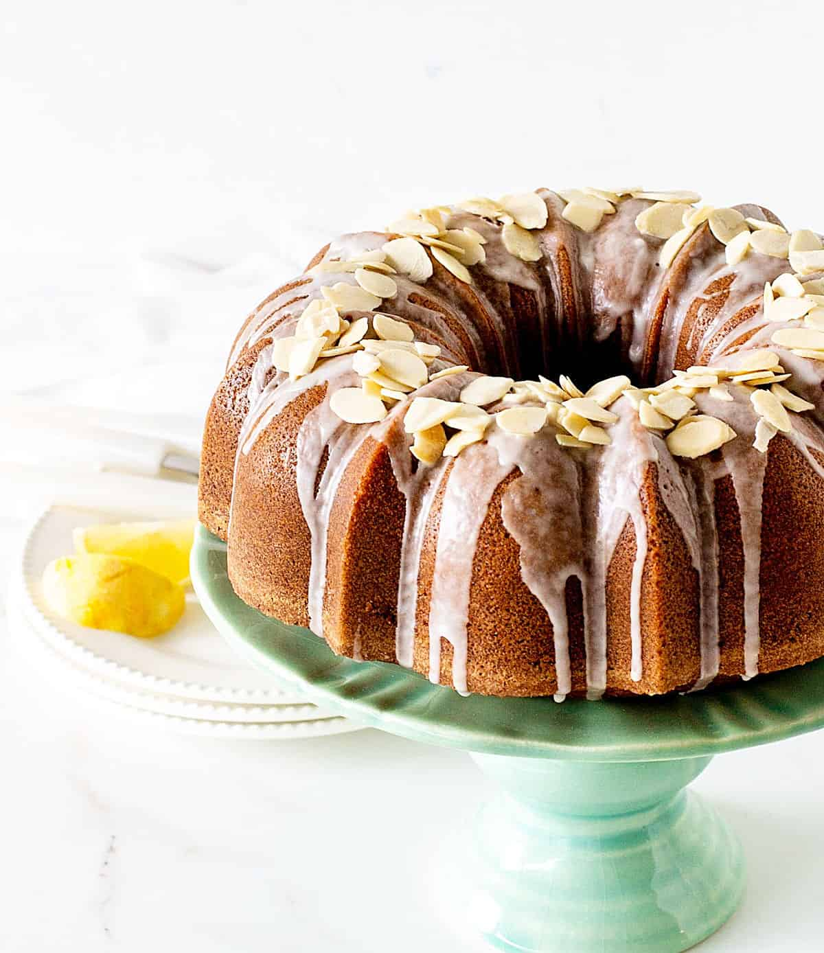 Partial view of almond topped glazed bundt cake on greenish cake stand, white background and surface, lemon wedges