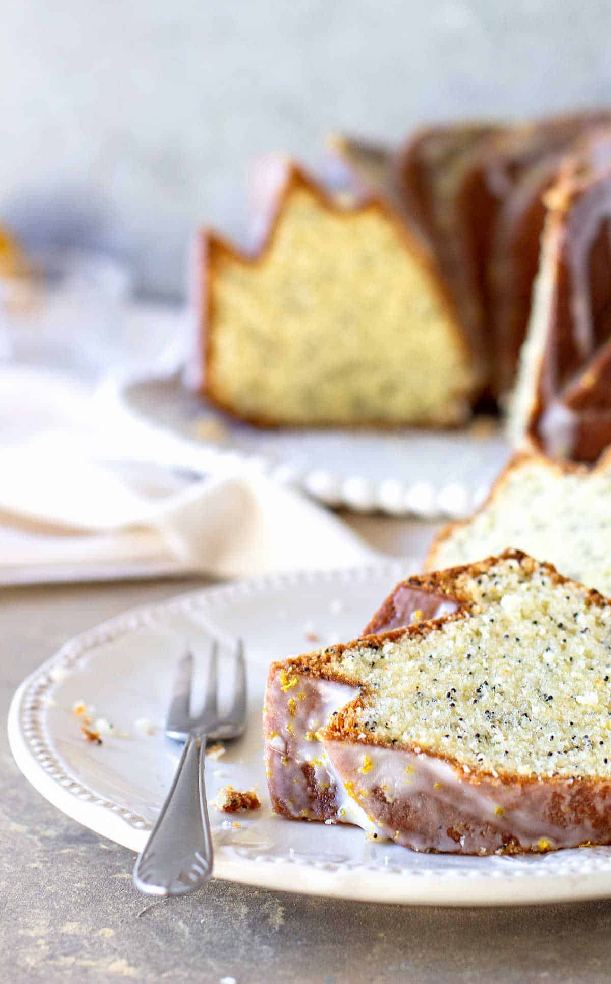 Partial view of lemon poppy seed bundt cake and slice on white plates, a fork and napkin, grey background