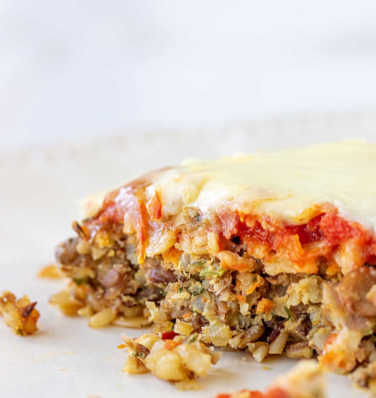 Eaten cheese lentil burger on parchment paper, white grey background