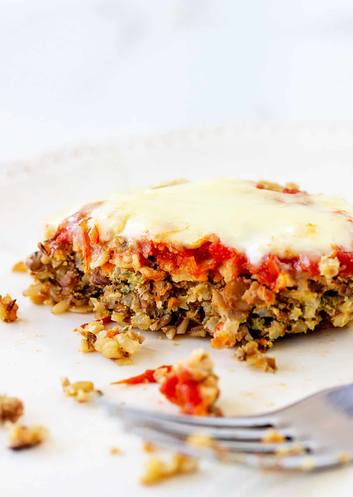 White plate with half a cheese and tomato topped lentil burger, a fork
