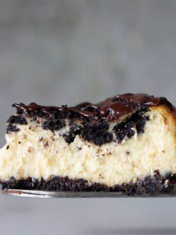Single slice of oreo cheesecake with grey background