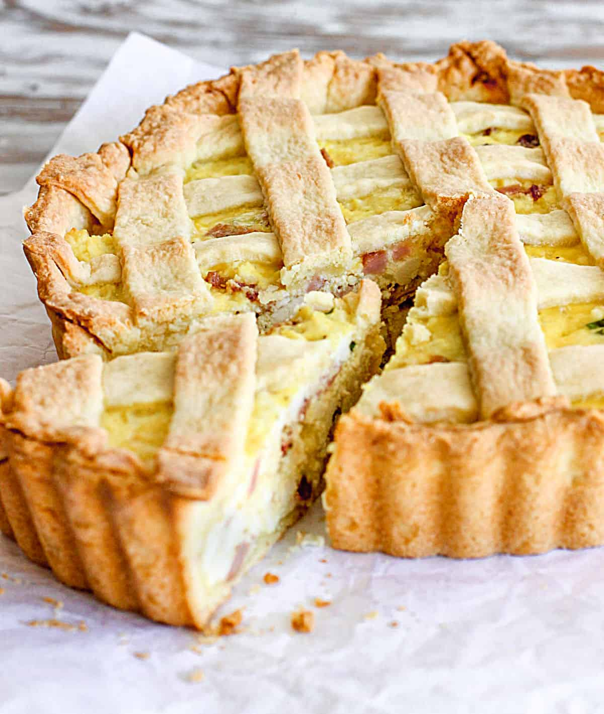 Whole lattice ricotta pie with one slice coming out on a white paper