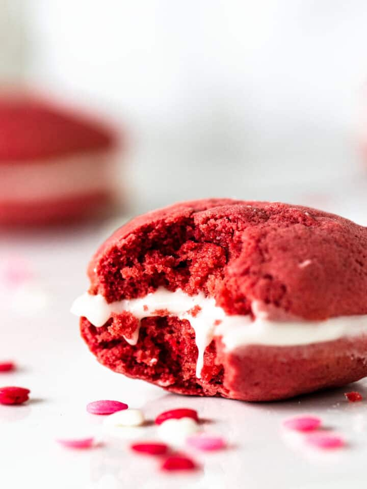 Close up of eaten red velvet whoopie pie, white marble surface, pink and red confetti around