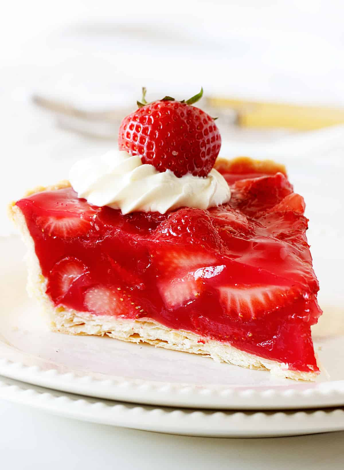 Single slice of strawberry jello pie on white plate with white background