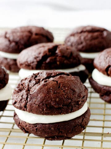 A wire rack with several chocolate whoopie pies with creamy filling