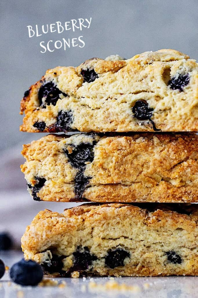 Close up of stack of blueberry scones with grey background; white text overlay