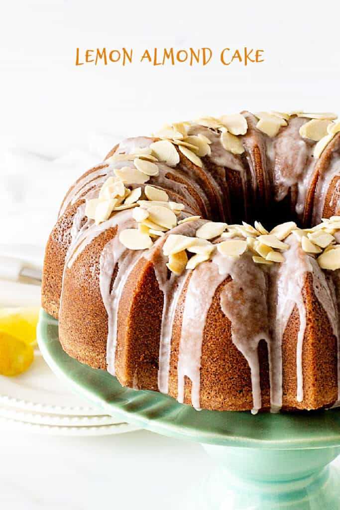Angle view of almond topped bundt cake with glaze on green cake stand; white background