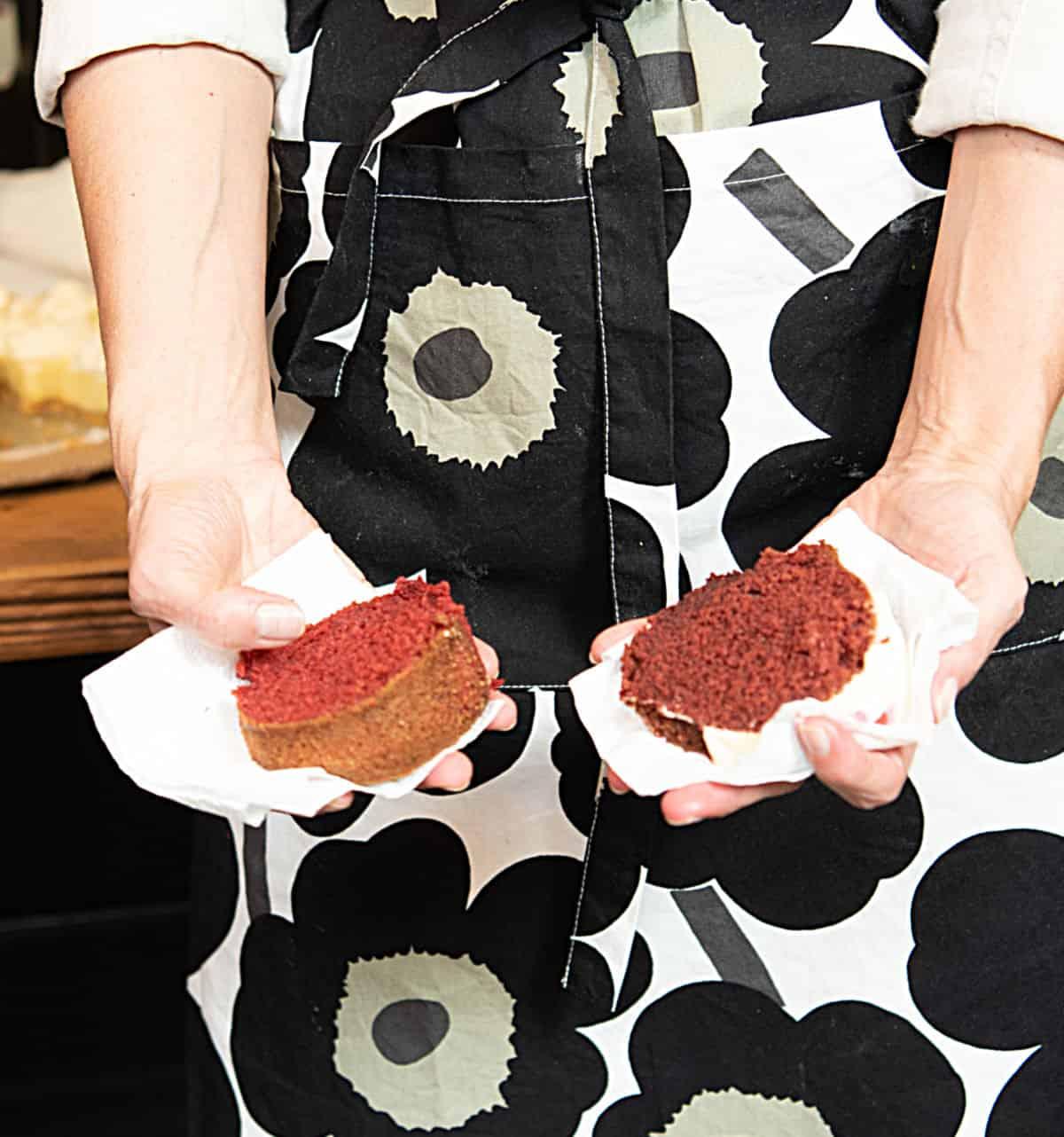Holding slices of red velvet cake, one in each hand, dark flowered apron