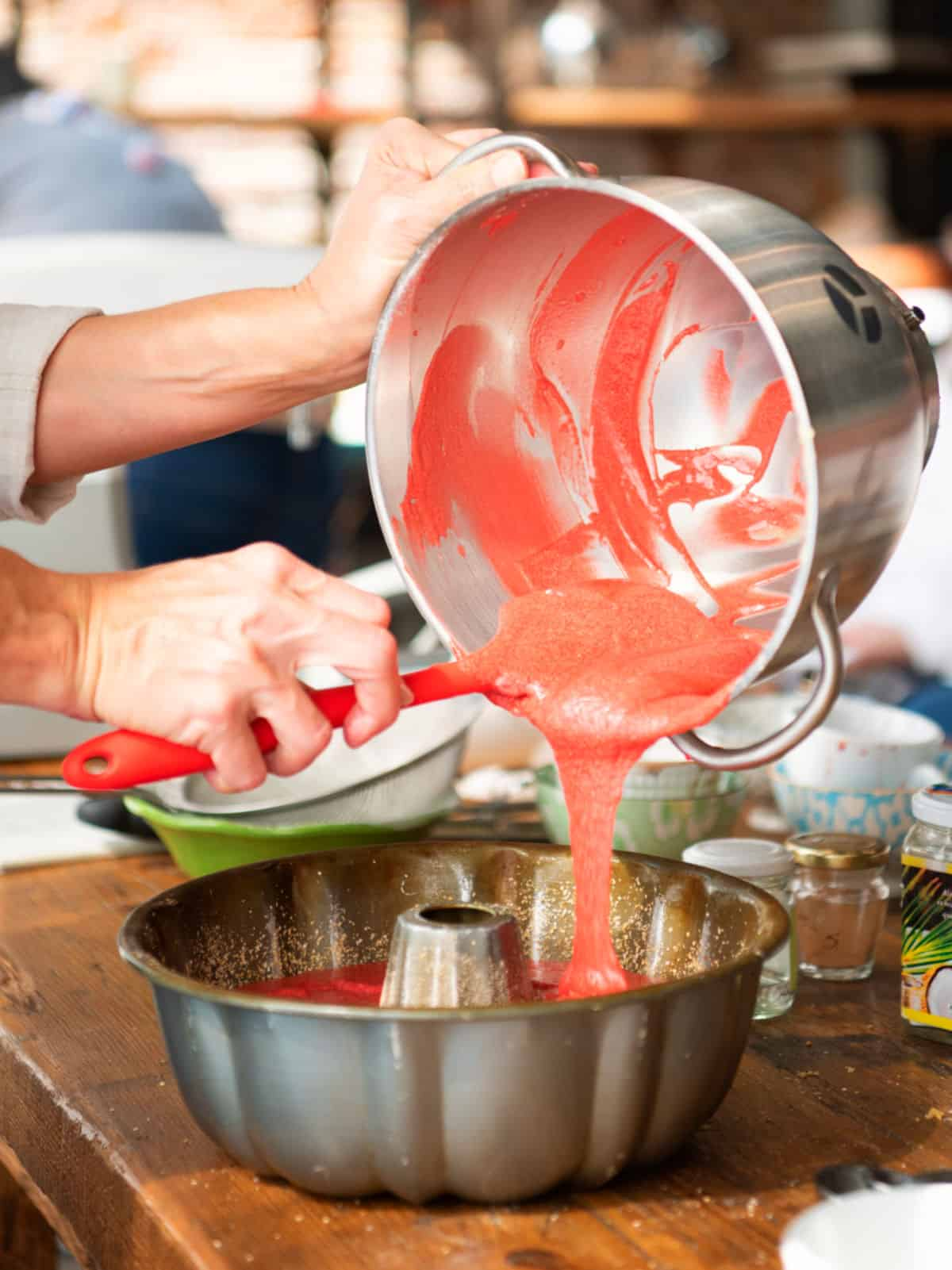 Pouring red cake batter into metal bundt pan from stand mixer bowl