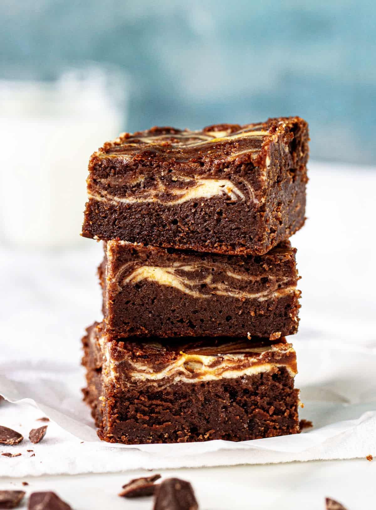 Stack of three cheesecake brownies on white surface, blueish background