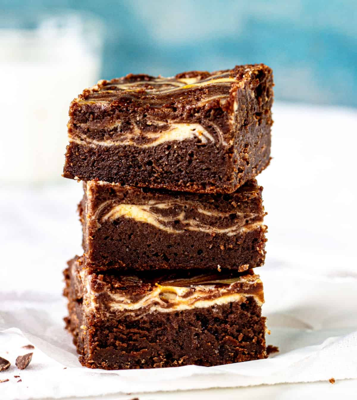 Cheesecake brownies stacked with blue and white background