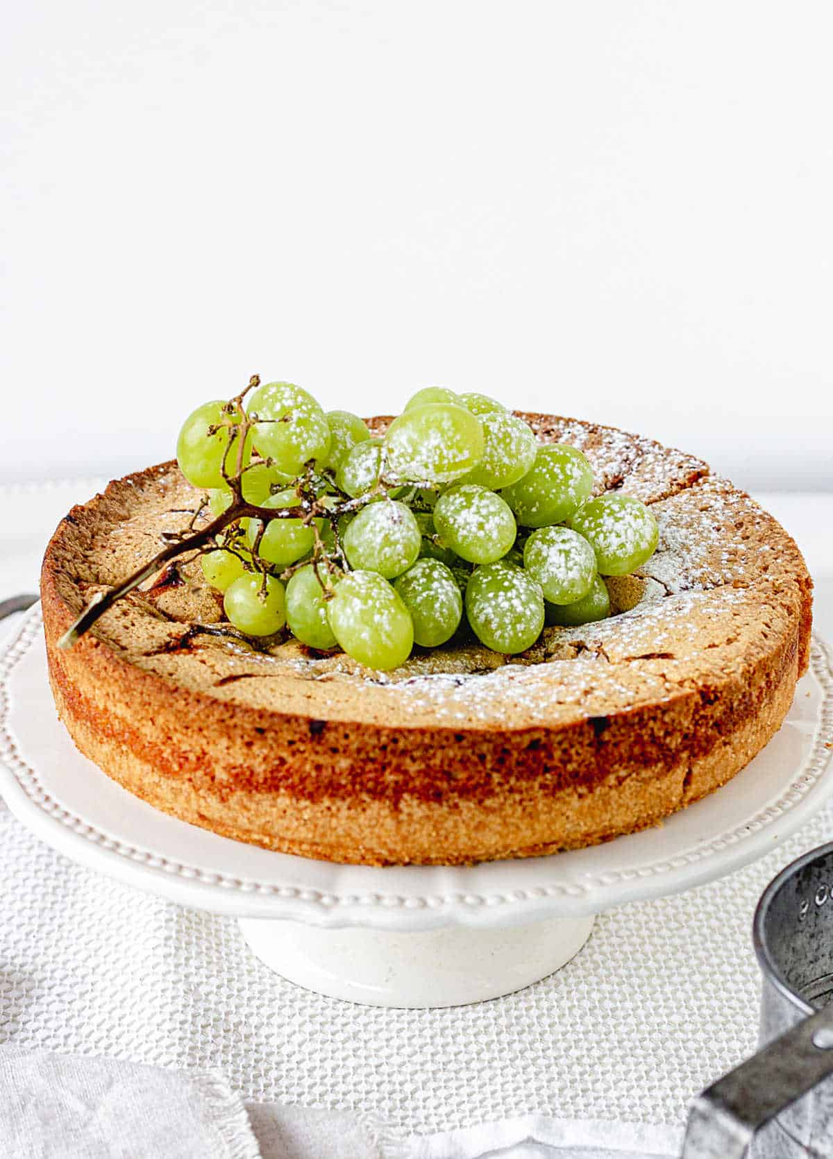 Bunch of green grapes on top of cake in white cake stand; white background