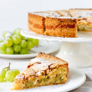 Slice of cake in white cake, rest in white cake stand, bunch of grapes, white background