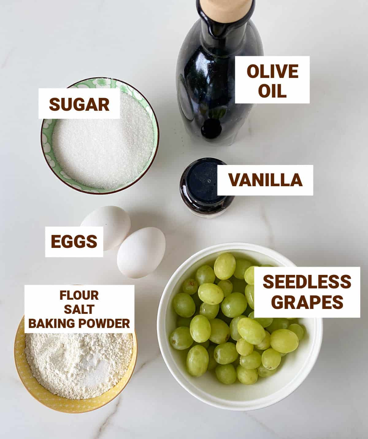 Bowls with ingredients for grape cake on white marble surface including olive oil and eggs