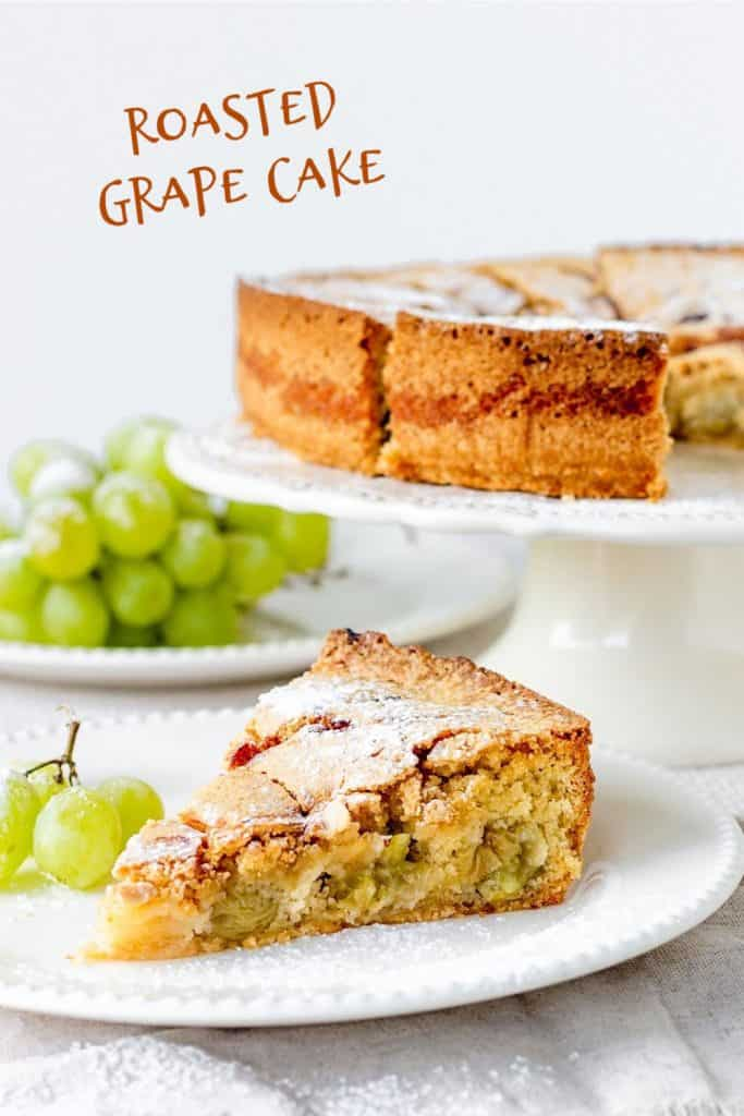 Slice of cake in white plate, cake in white cake stand, bunch of grapes, white background, text overlay