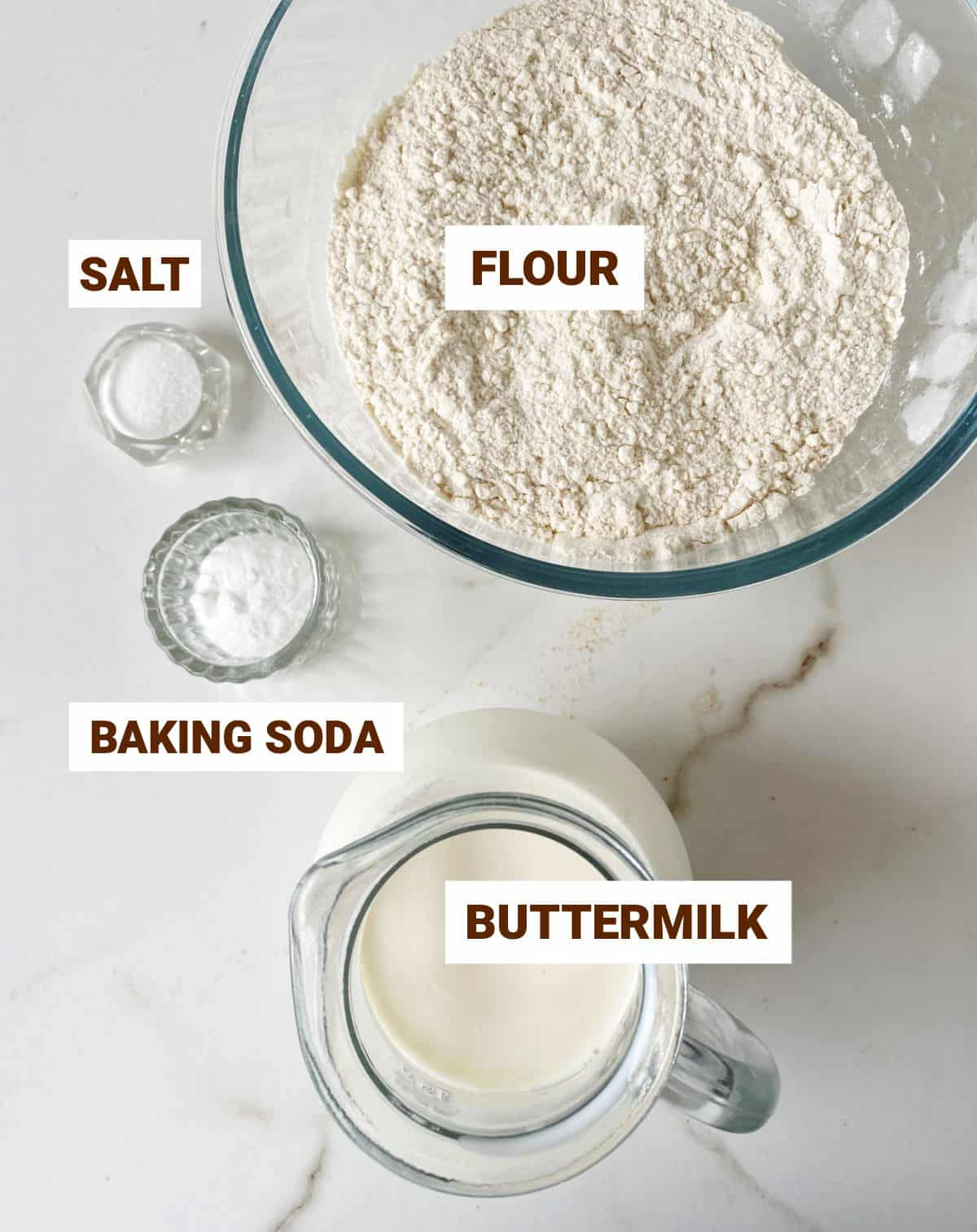 White marble surface with bowls containing ingredients for soda bread: buttermilk, flour, salt, baking soda