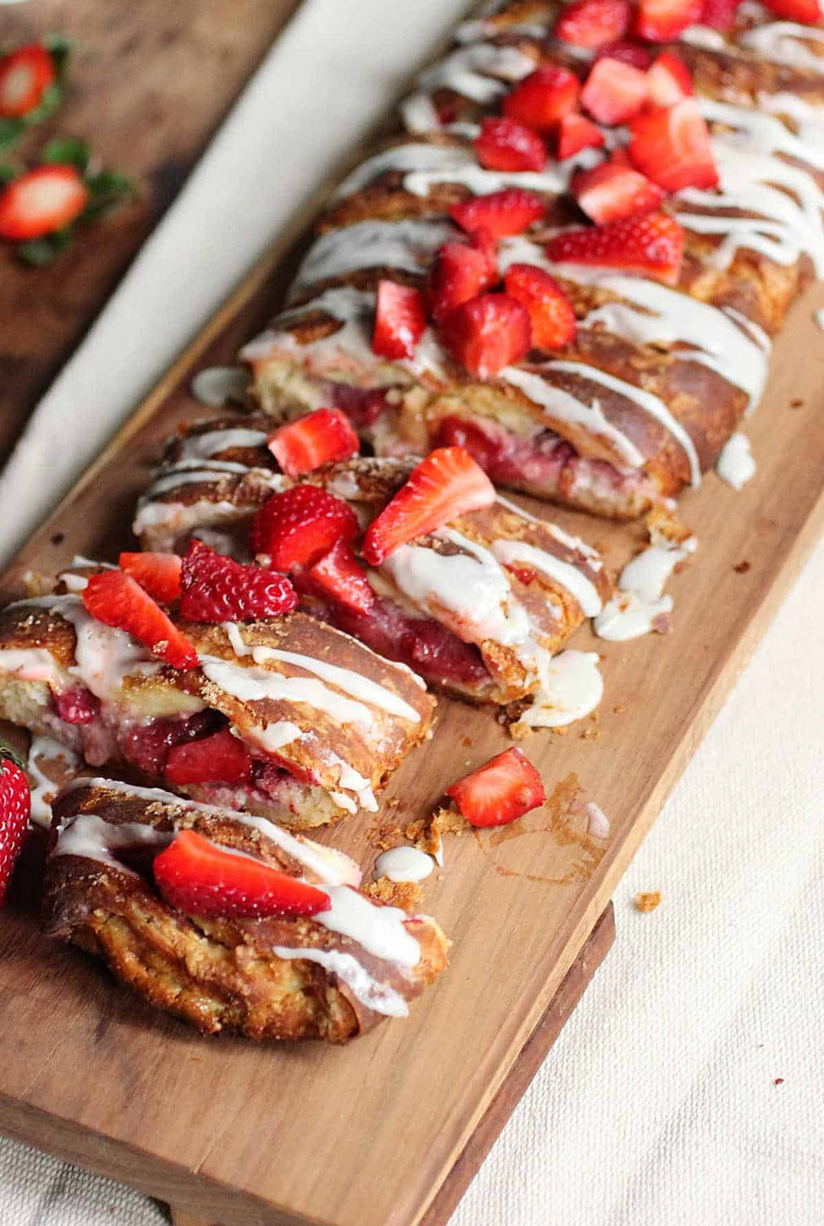 Top view of long strawberry topped danish on wooden board