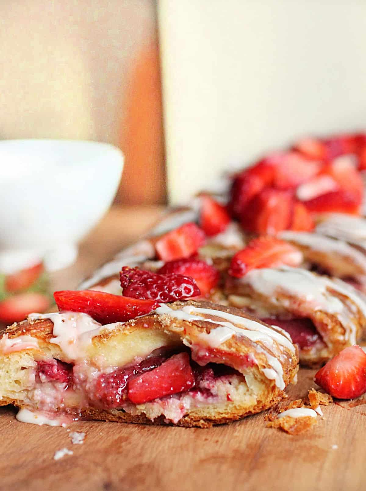 Sliced strawberry danish braid on wooden board, white bowl in background