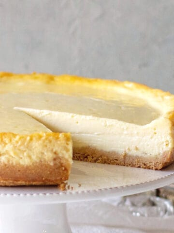Plain cheesecake missing a slice on a white cake stand, grey background