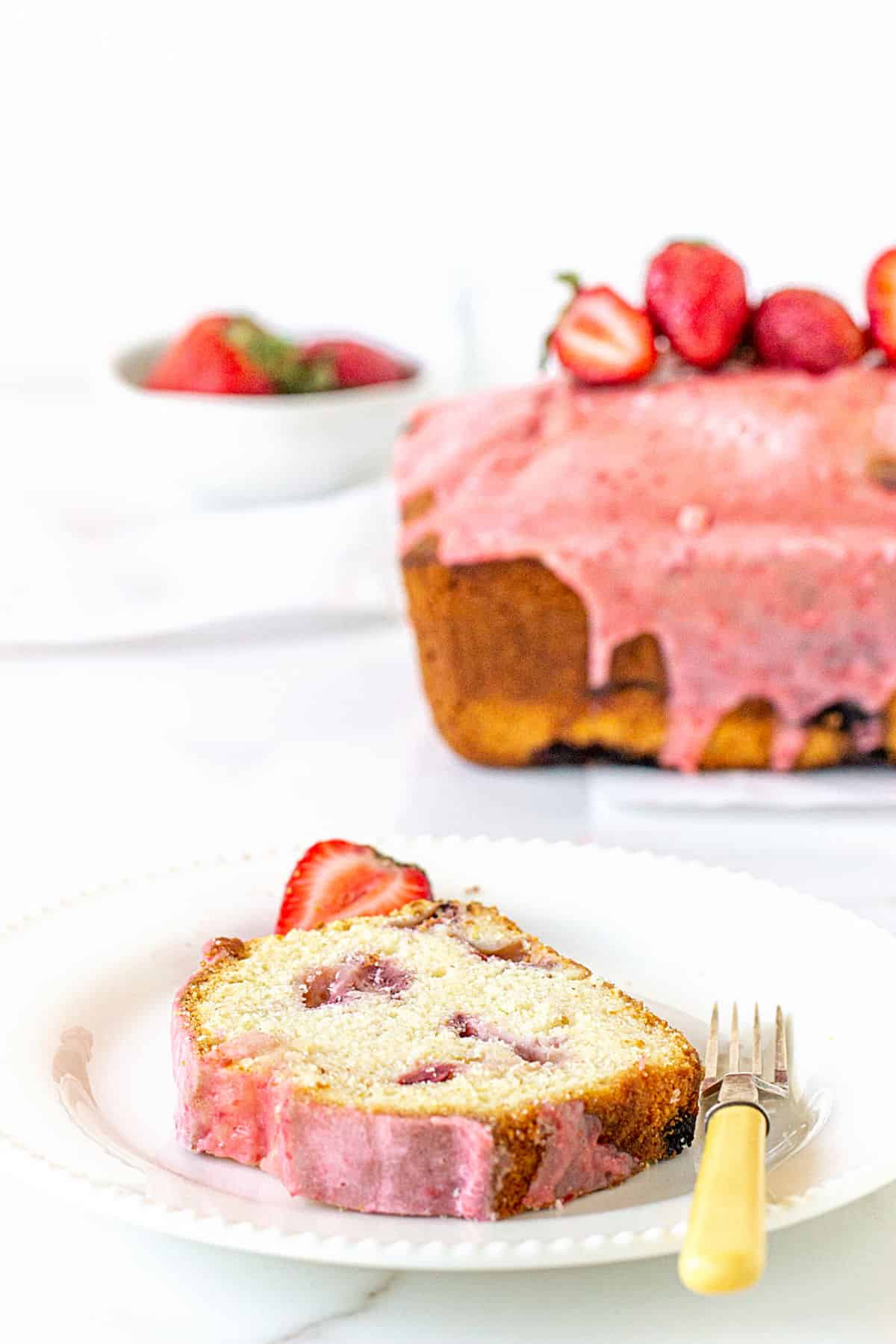A slice of strawberry cake in white plate, whole cake with strawberries in white background