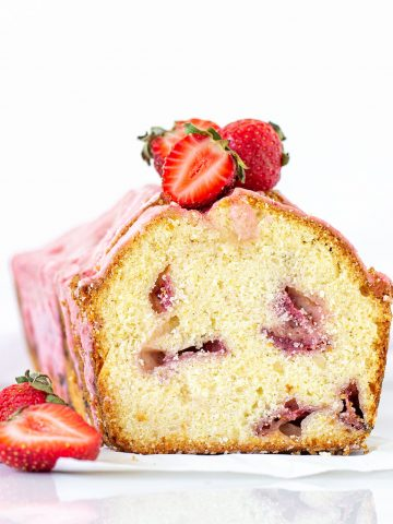 Front view of cut pound cake with strawberries and pink glaze; white background