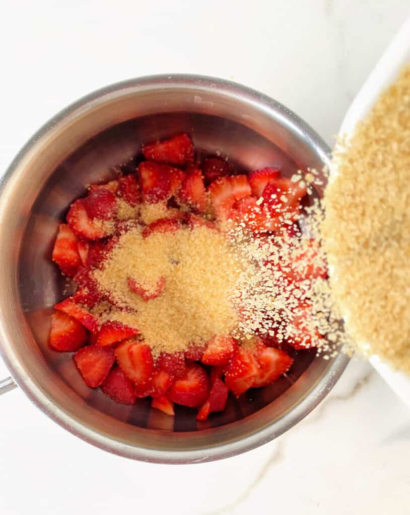 Adding light brown sugar to metal saucepan with chopped strawberries, white background