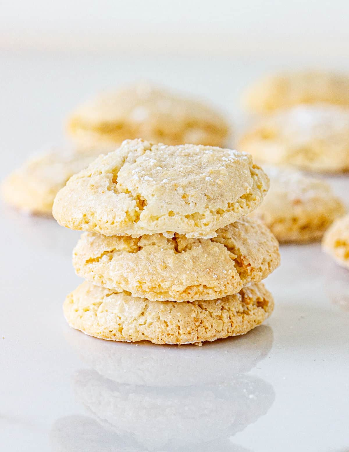 Stack of three amaretti cookies on white marble with more cookies in background
