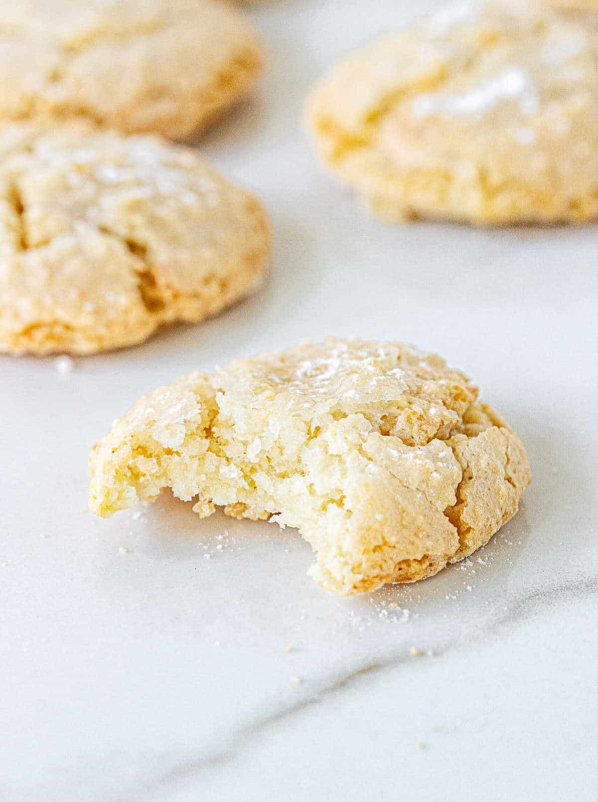Bitten almond cookie and whole ones on white marble surface
