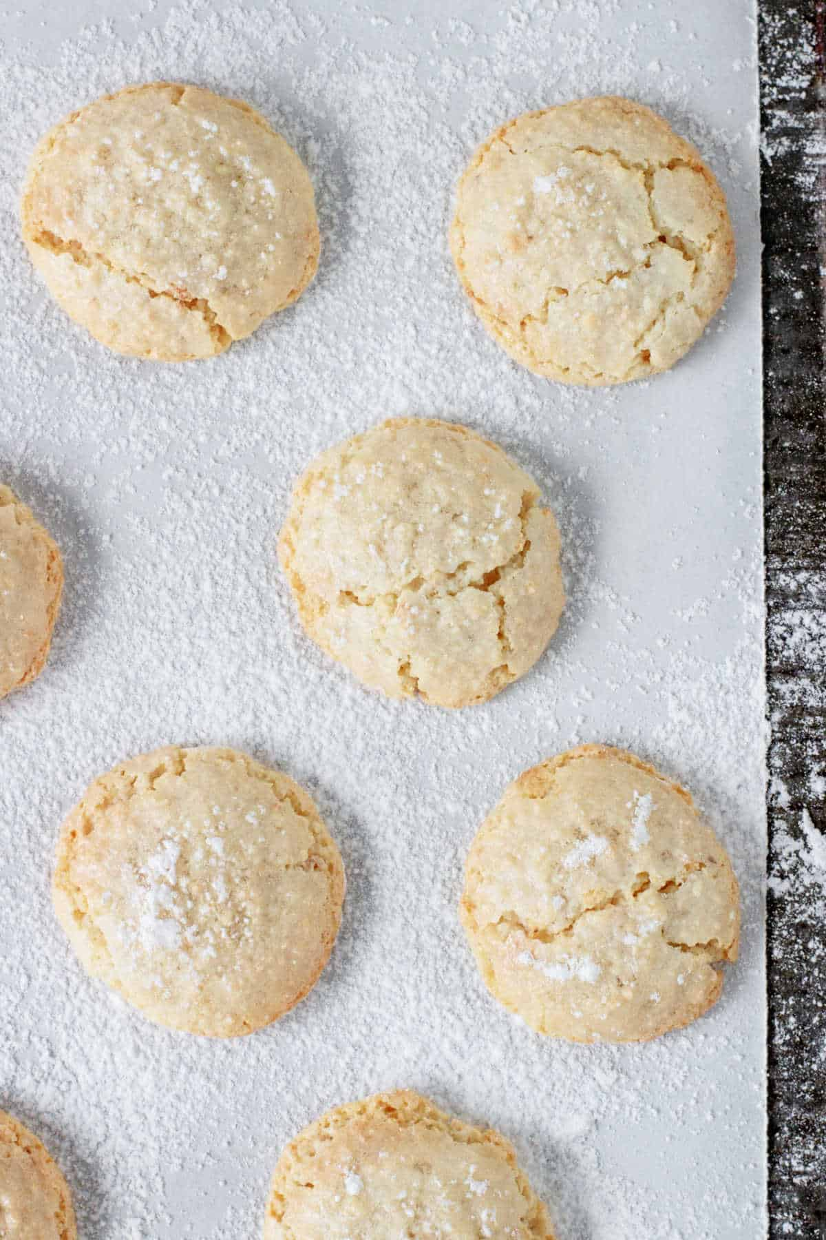 Top view of crackled almond cookies on white parchment paper