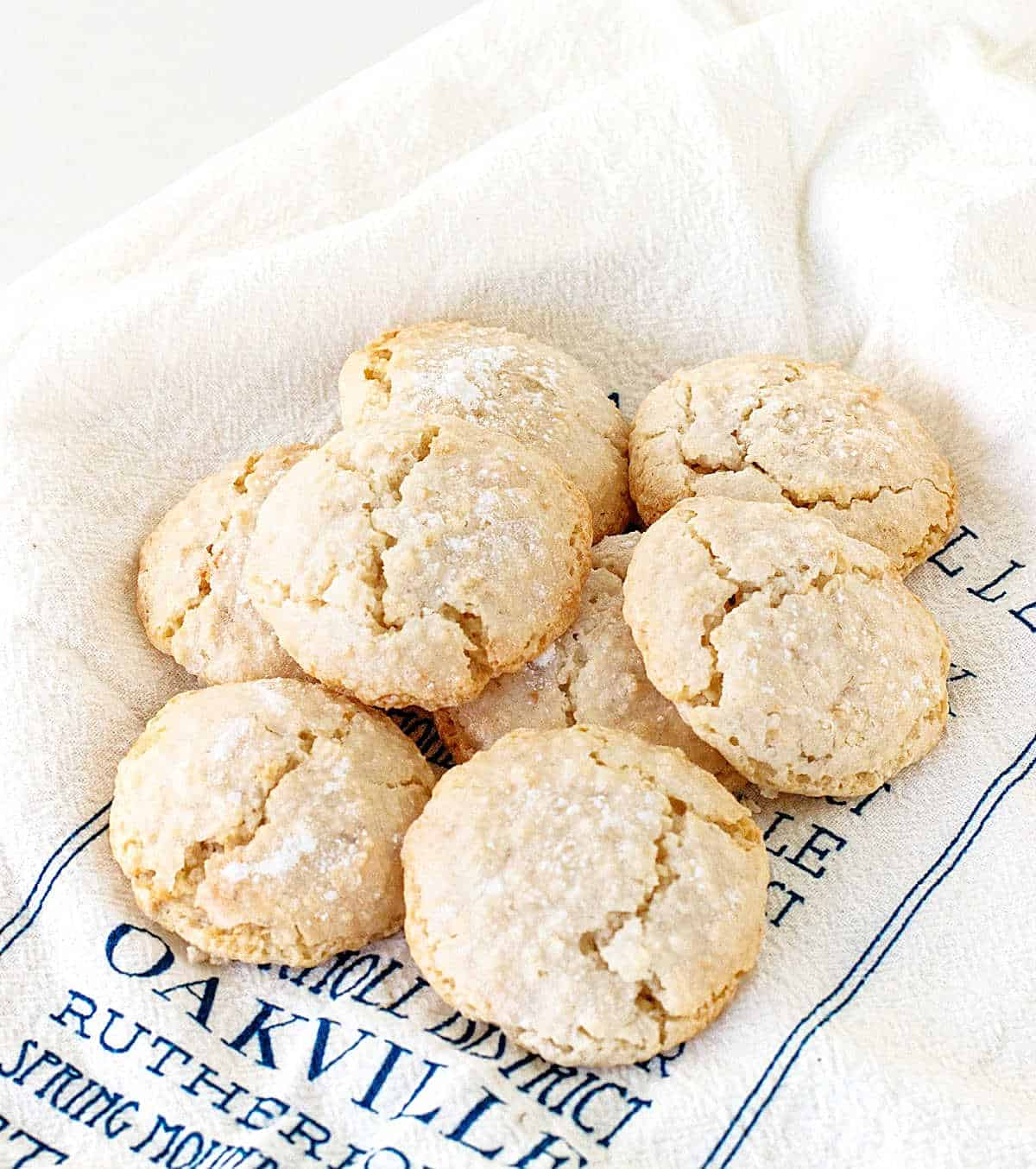 Several almond crinkled cookies on white and blue kitchen towel