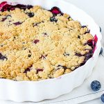Partial view of round white dish with bluberry crumb cake, white surface, loose blueberries