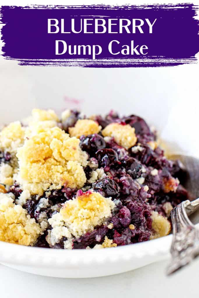 Close up of white bowl with blueberry dump cake serving, a silver spoon, white background, purple text overlay