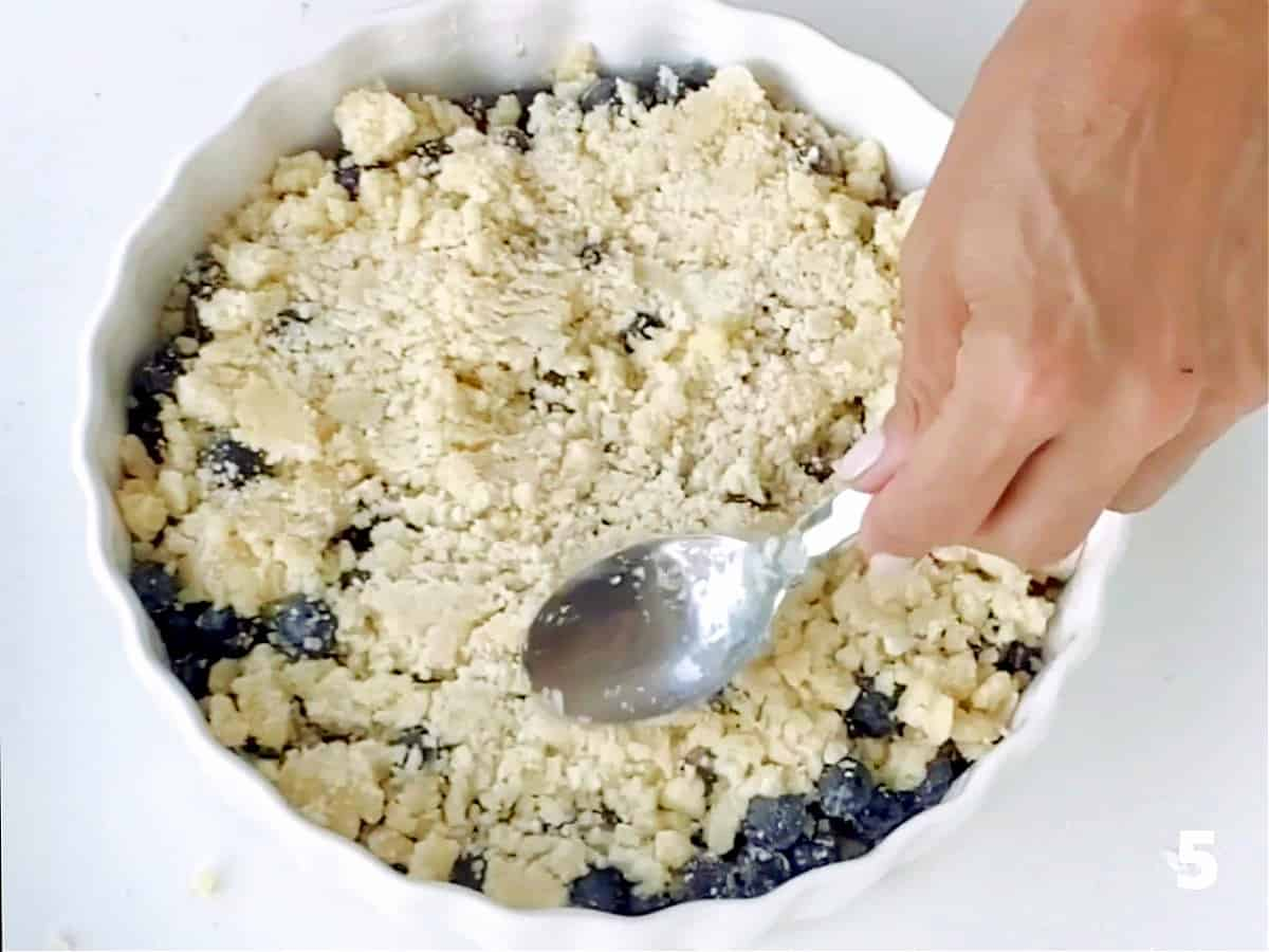 Pressing crumble mixture with spoon on top of blueberries in white ceramic dish on white surface