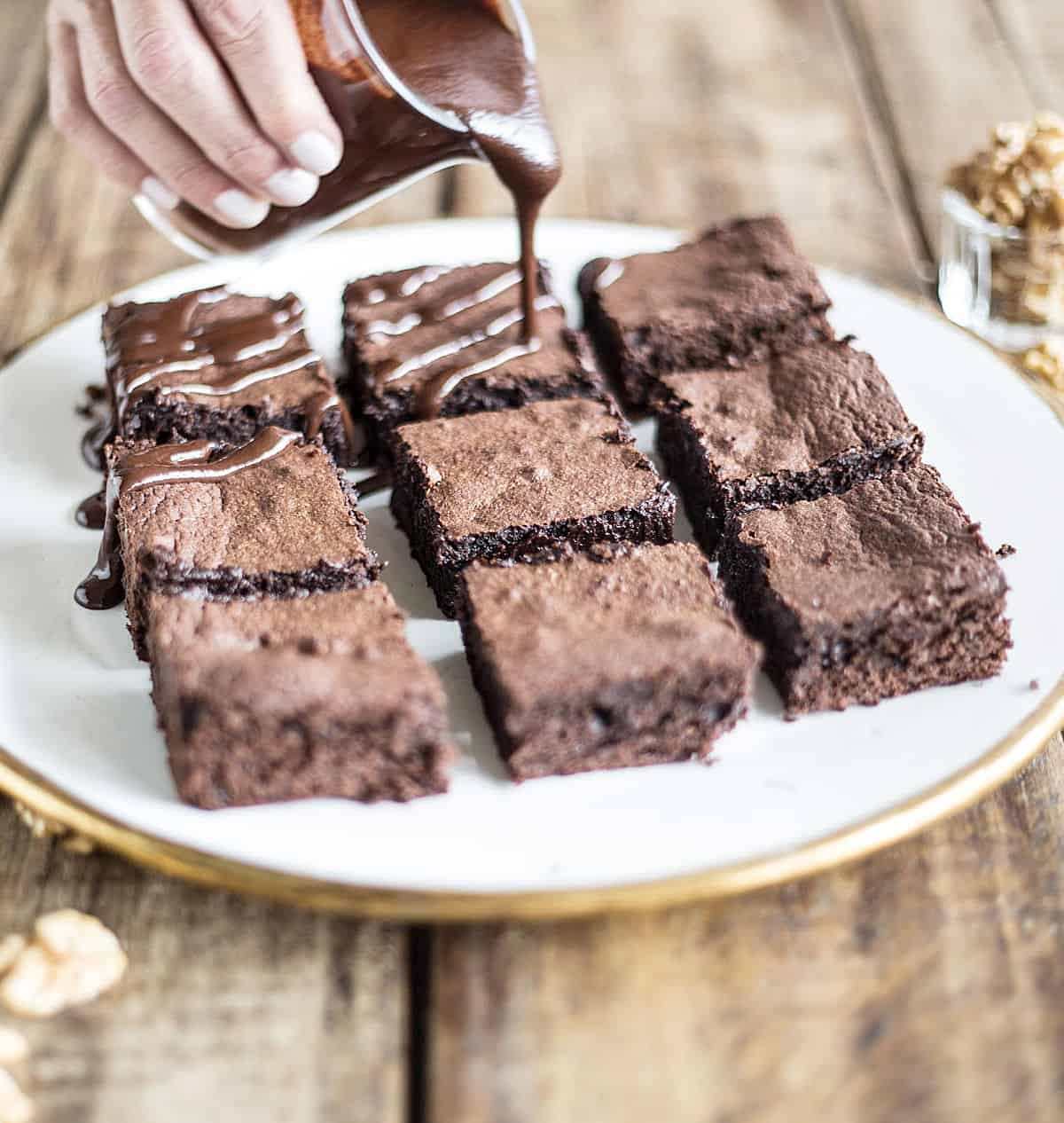 Pouring chocolate sauce over brownie squares on white plate on a wooden table