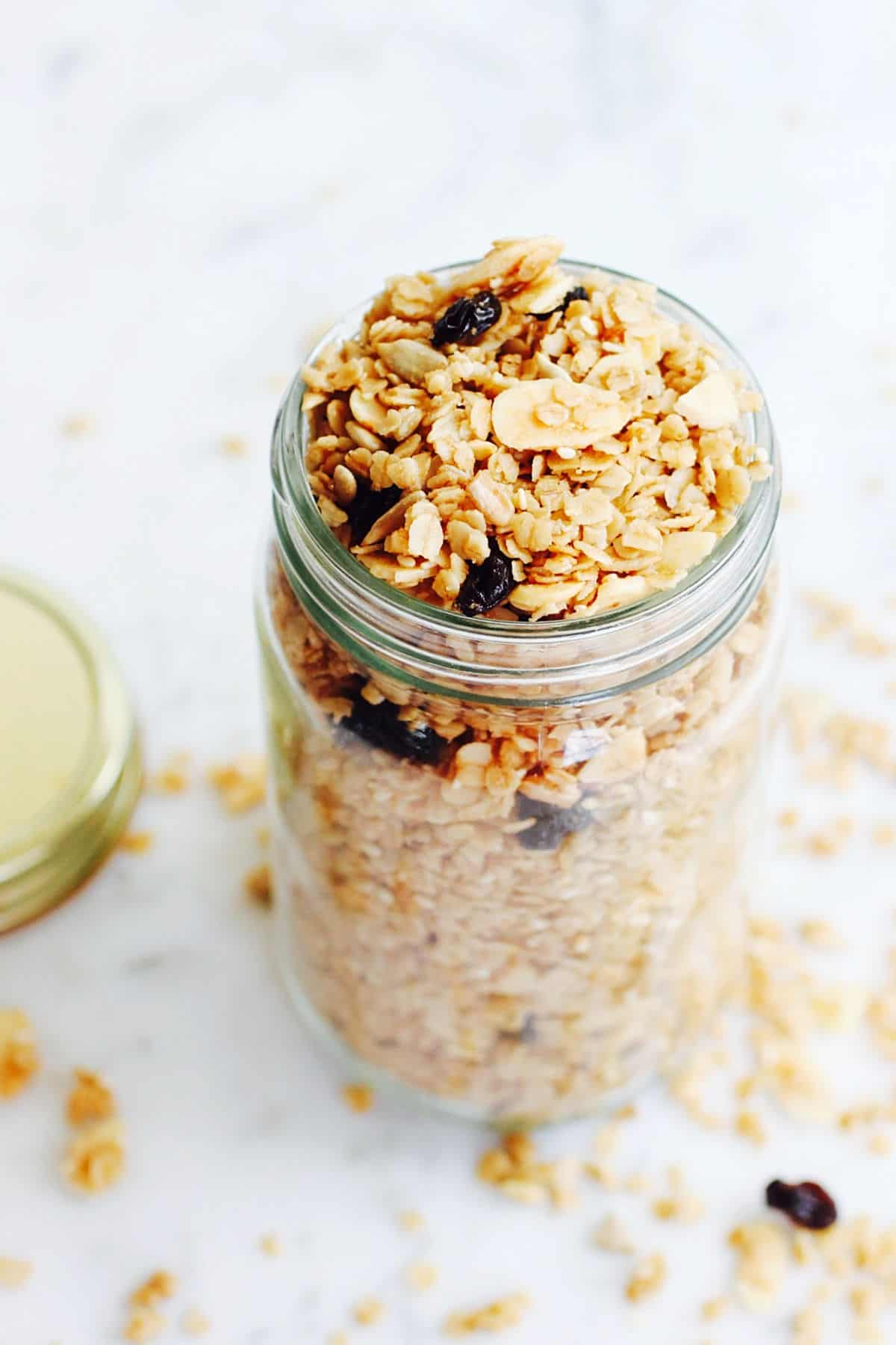 Tall glass jar with granola on a white surface