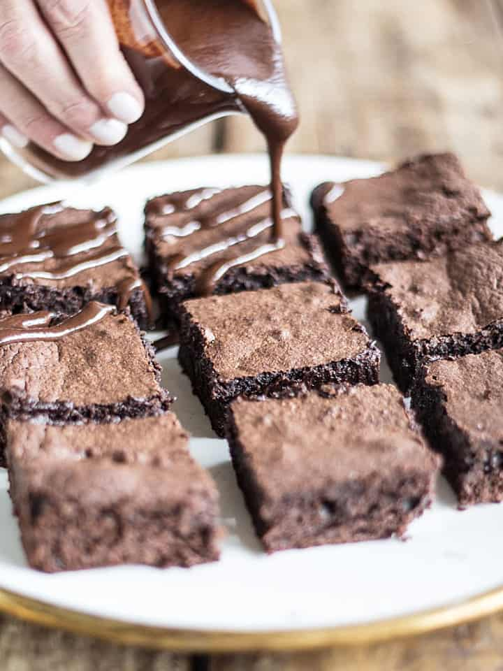 Hand pouring chocolate sauce on brownie squares in white plate on wooden table
