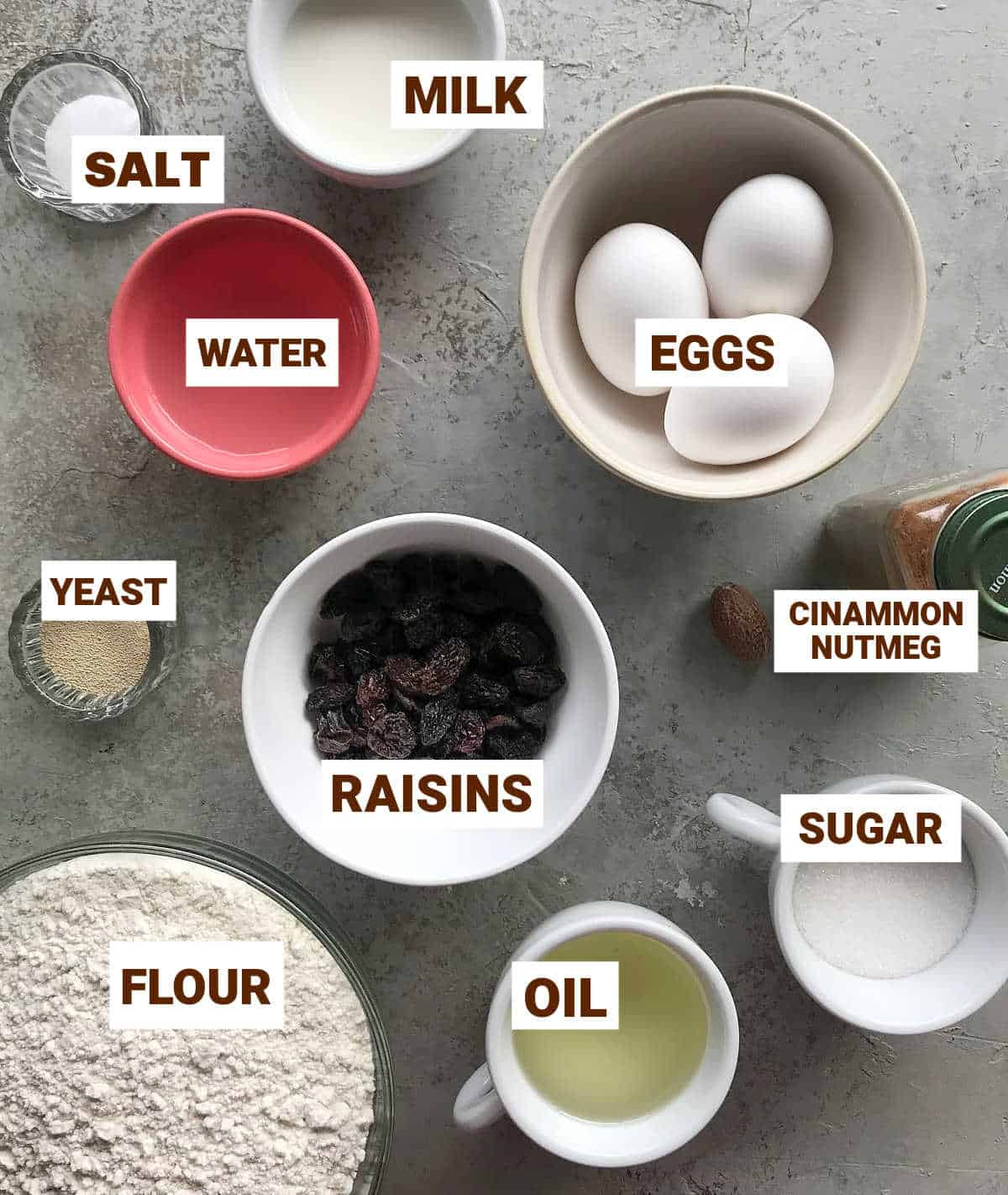 Bowls with sweet buns ingredients on grey background including raisins, eggs and yeast