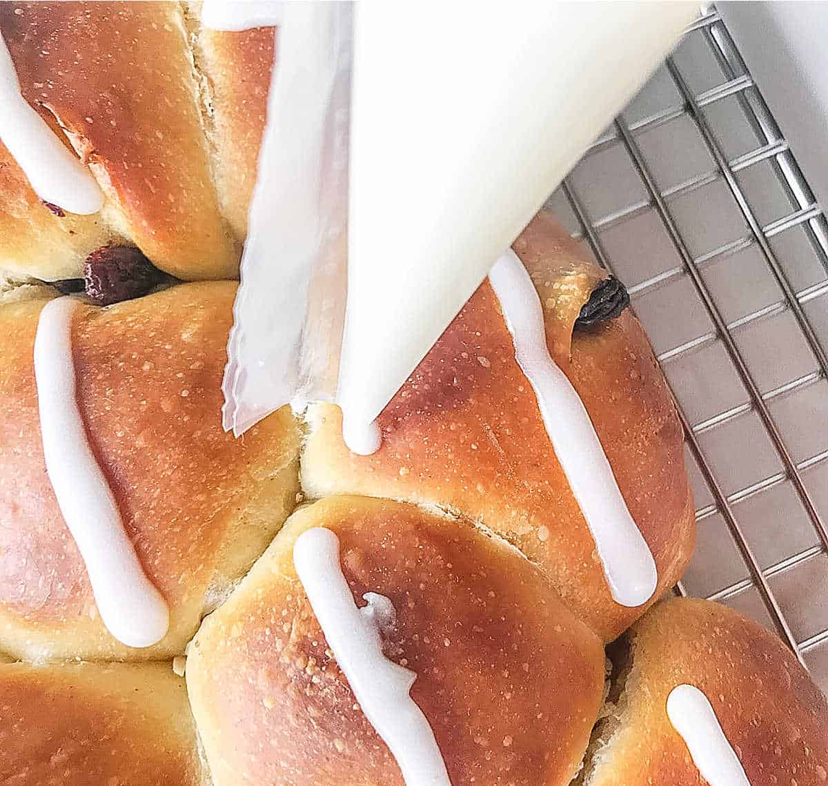 Piping white lines on baked small rolls