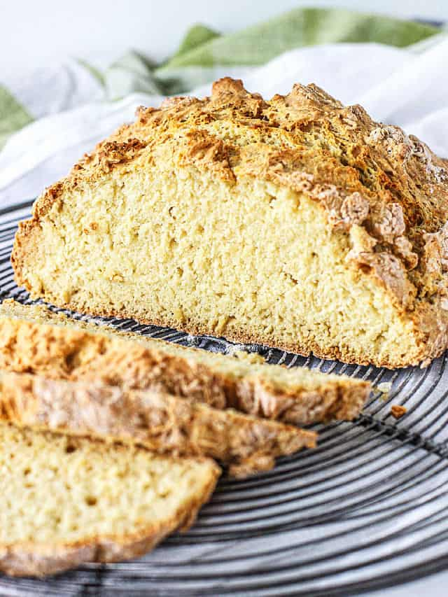 Slices and cut Irish soda bread on wire rack, white green background