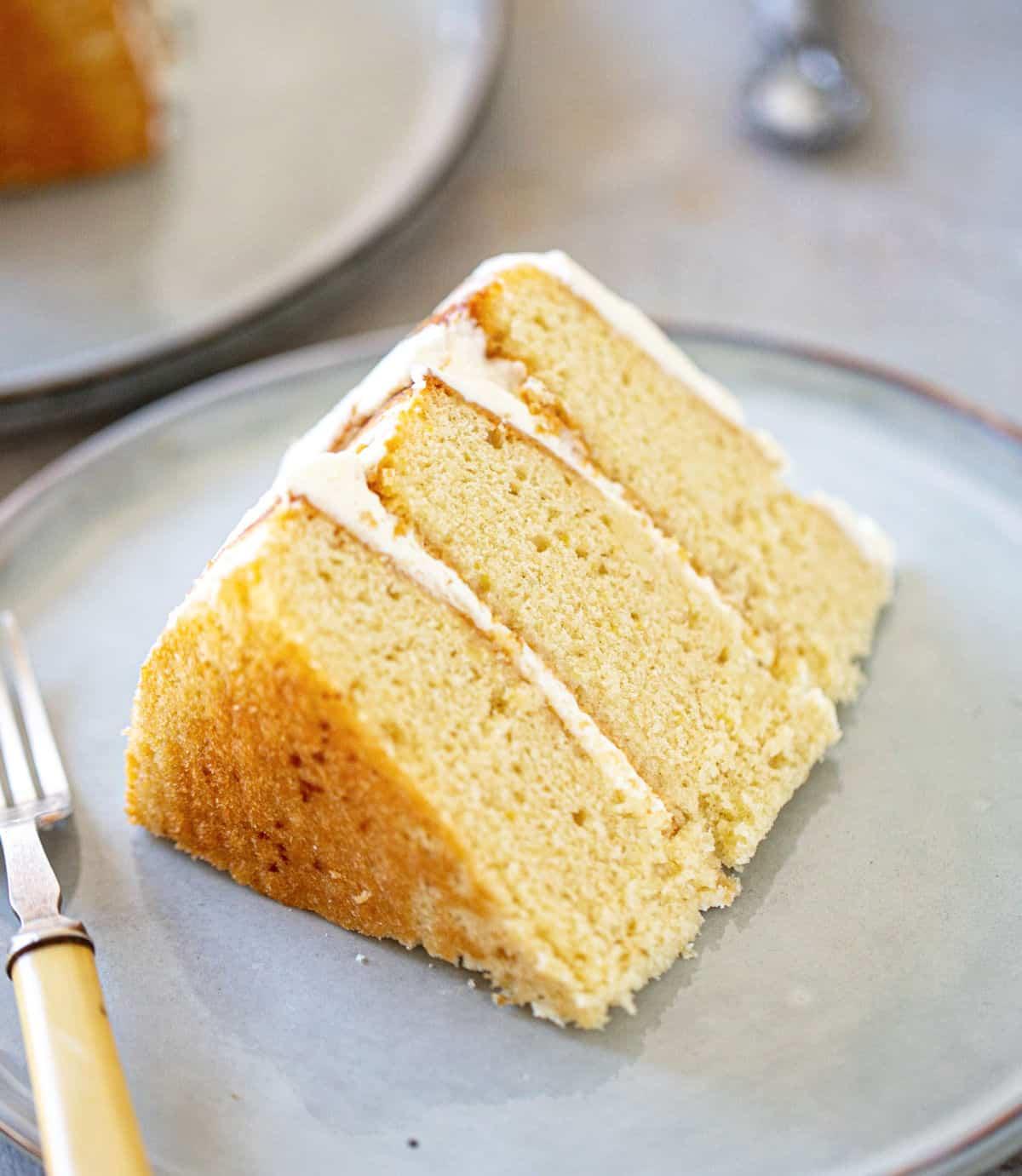 Close of slice of three layer lemon cream cake on grey plates and background