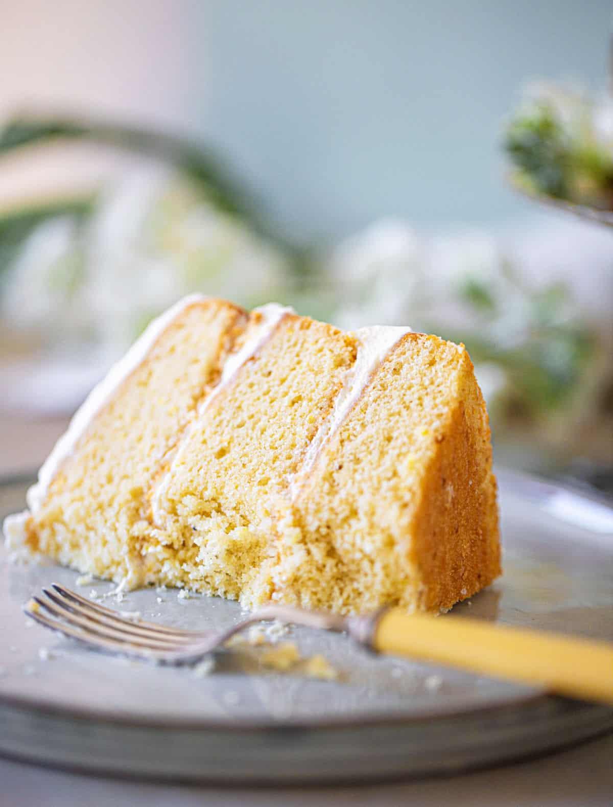 Eaten single slice of layer lemon cream cake with fork on grey plate