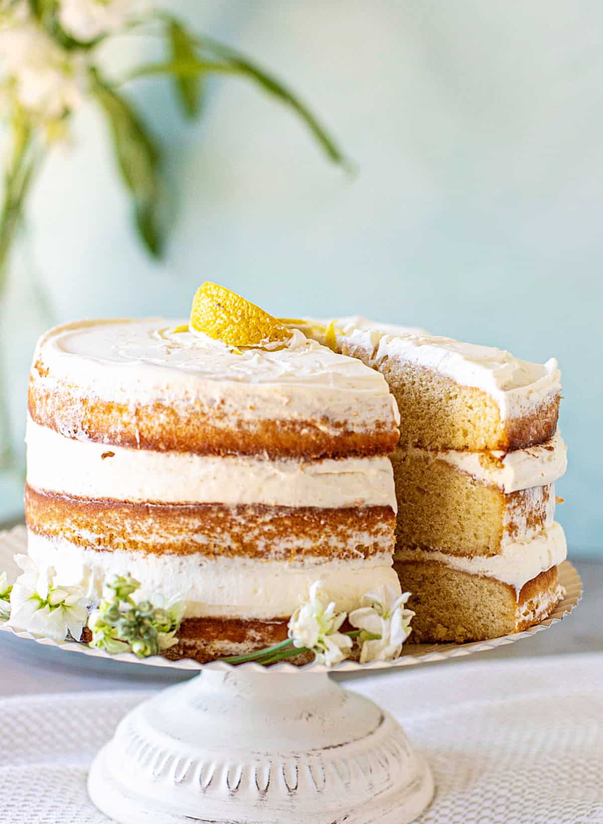 Whole naked cream layer cake on white cake stand, slice being pulled out, green aqua background