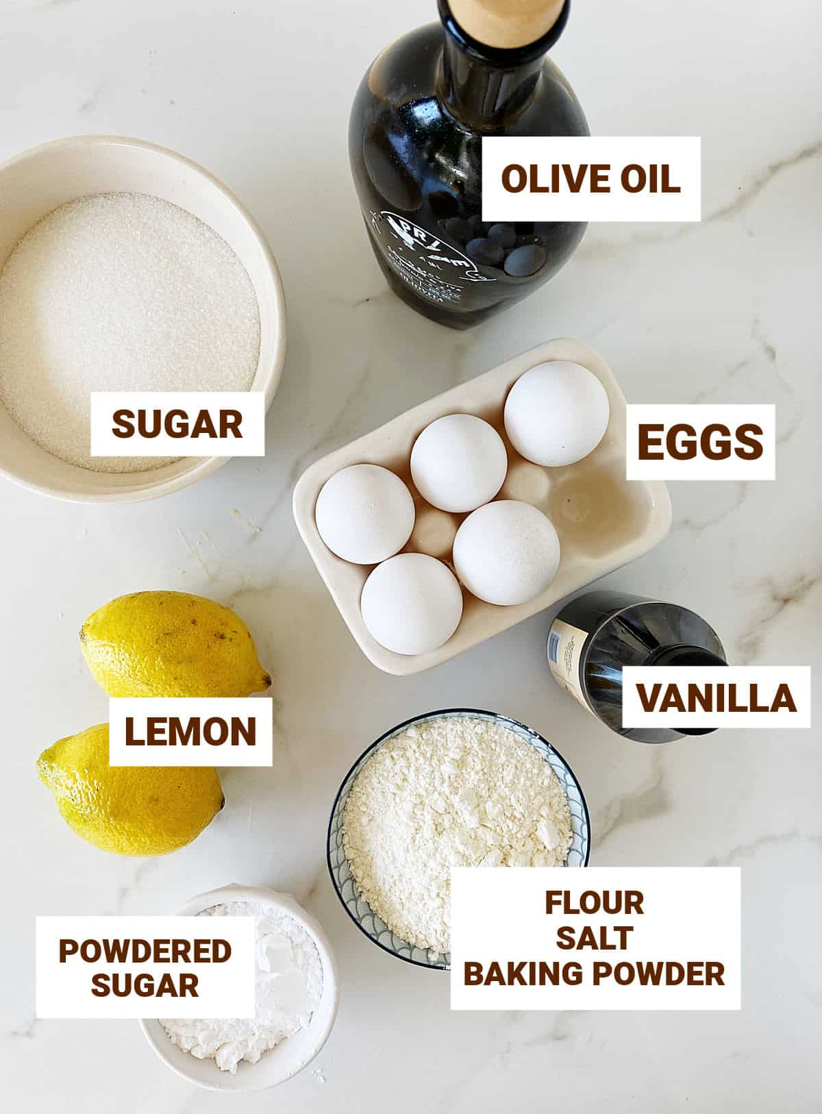 Ingredients for lemon olive oil cake in bowls and alone including eggs, vanilla and sugars