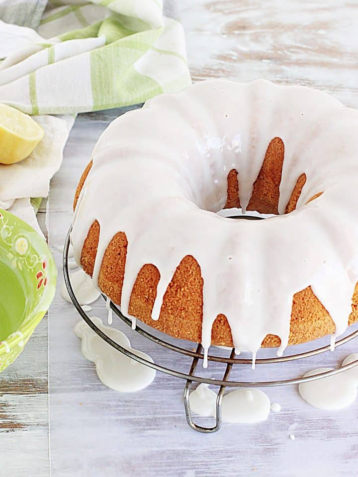 Glazed bundt cake on wire rack on white table, green white cloth and bowl